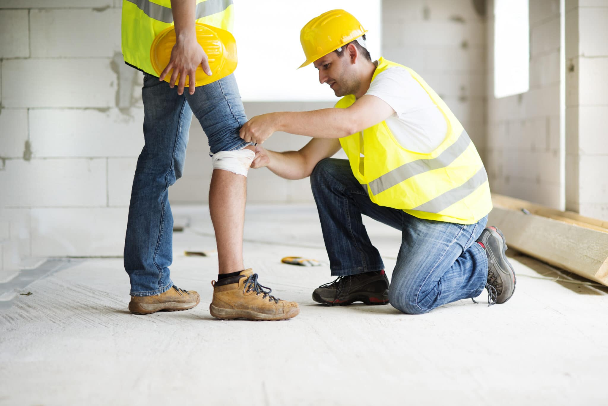 construction worker on job site bandaging coworker's knee