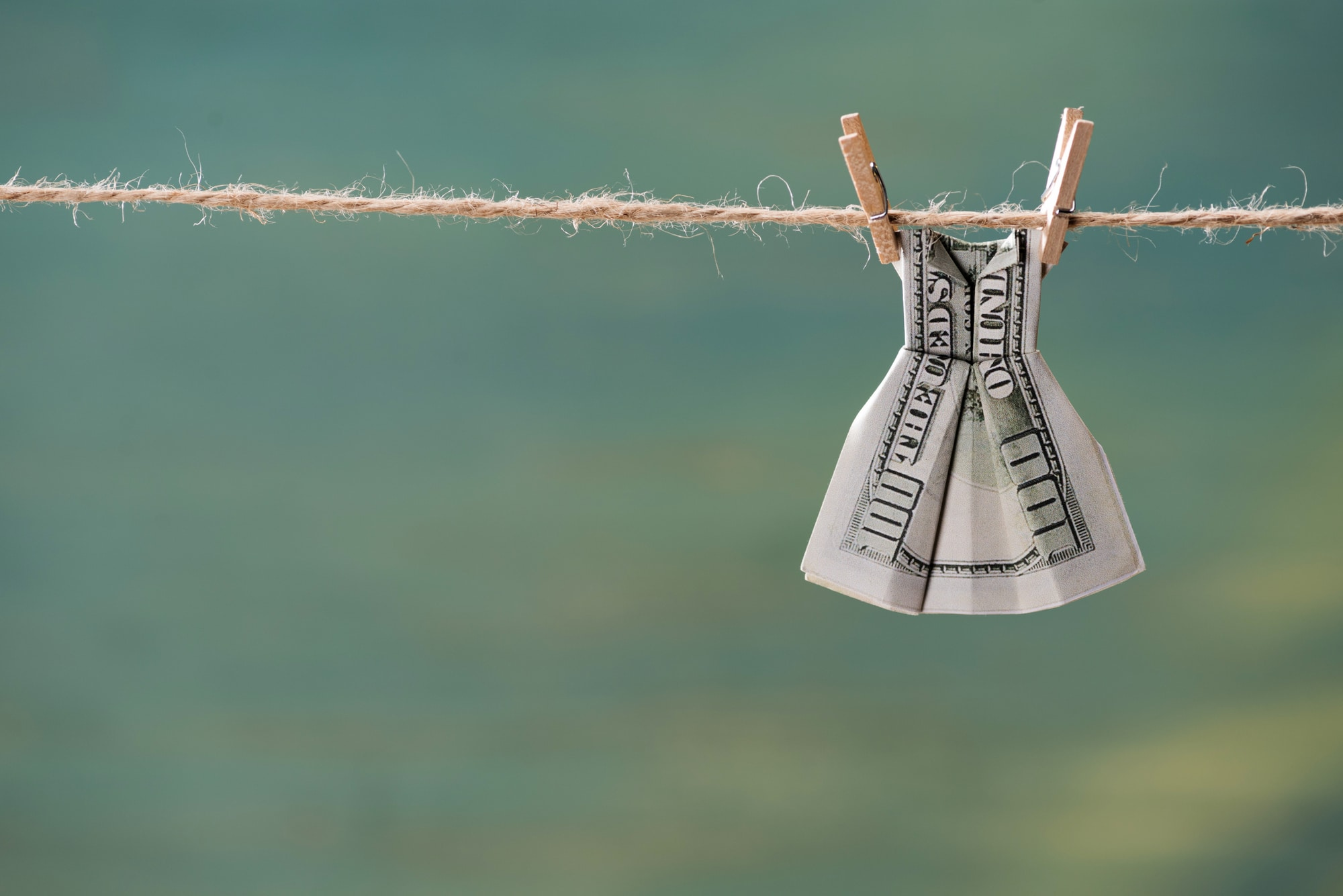 dollar bill folded into dress hanging on clothesline