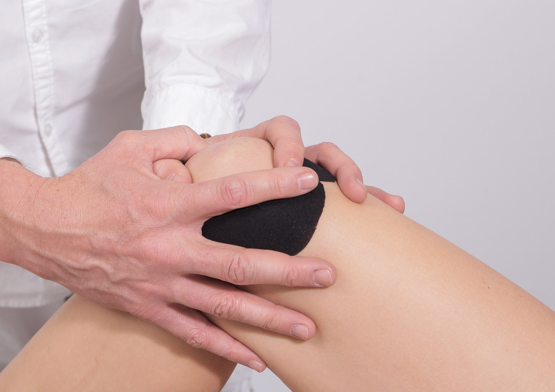 therapist taping and massaging woman's knee