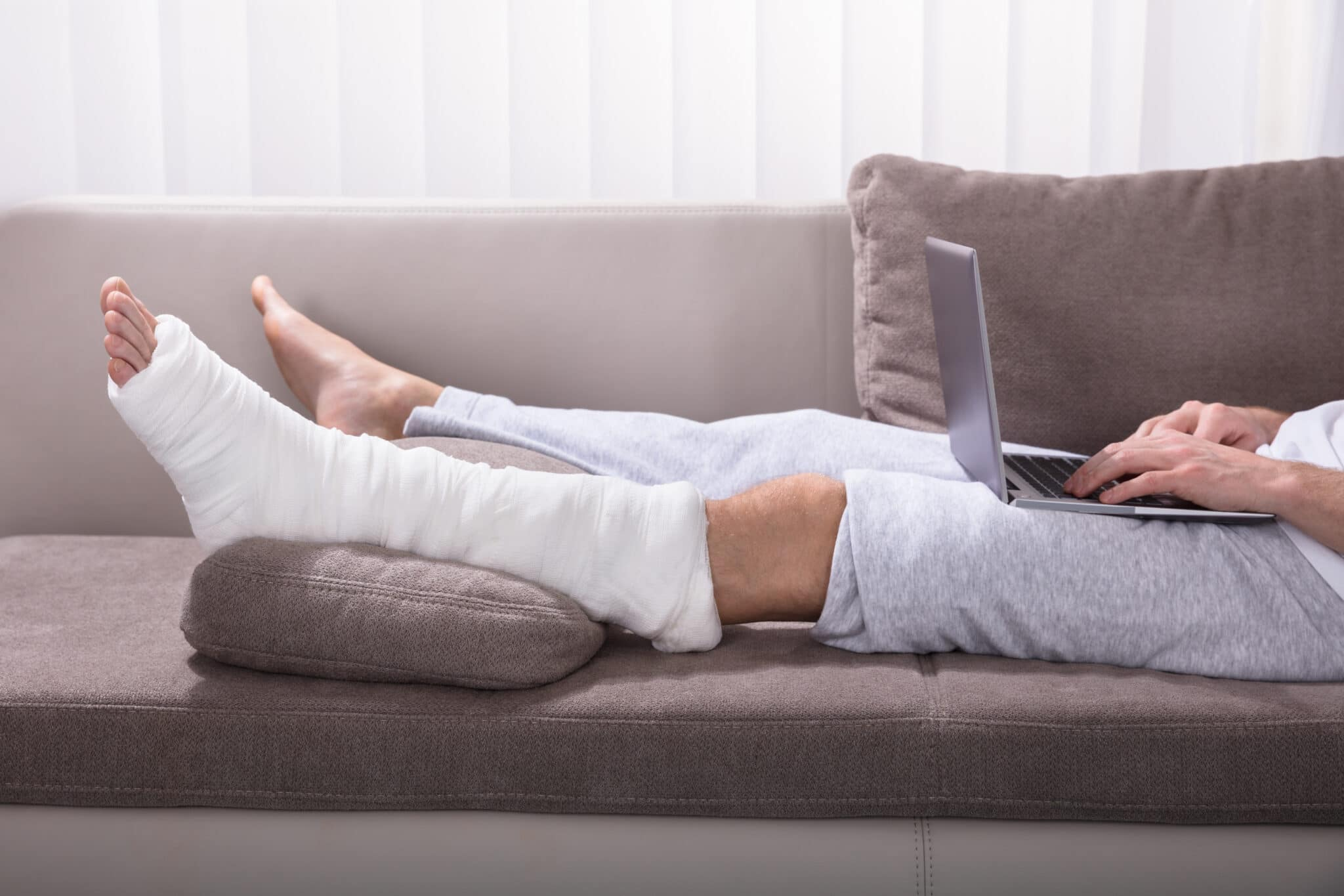 man with leg in cast sitting on sofa with laptop