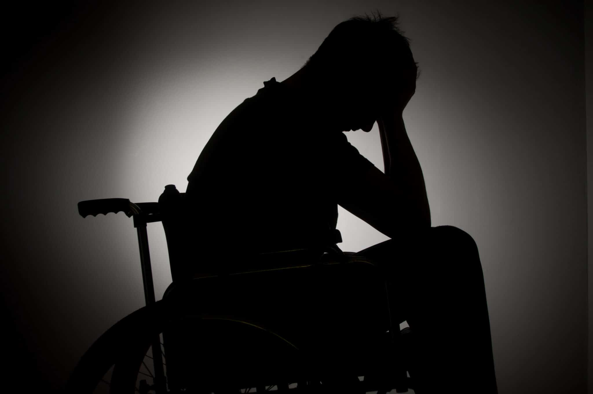 silhouette of sad man in wheelchair