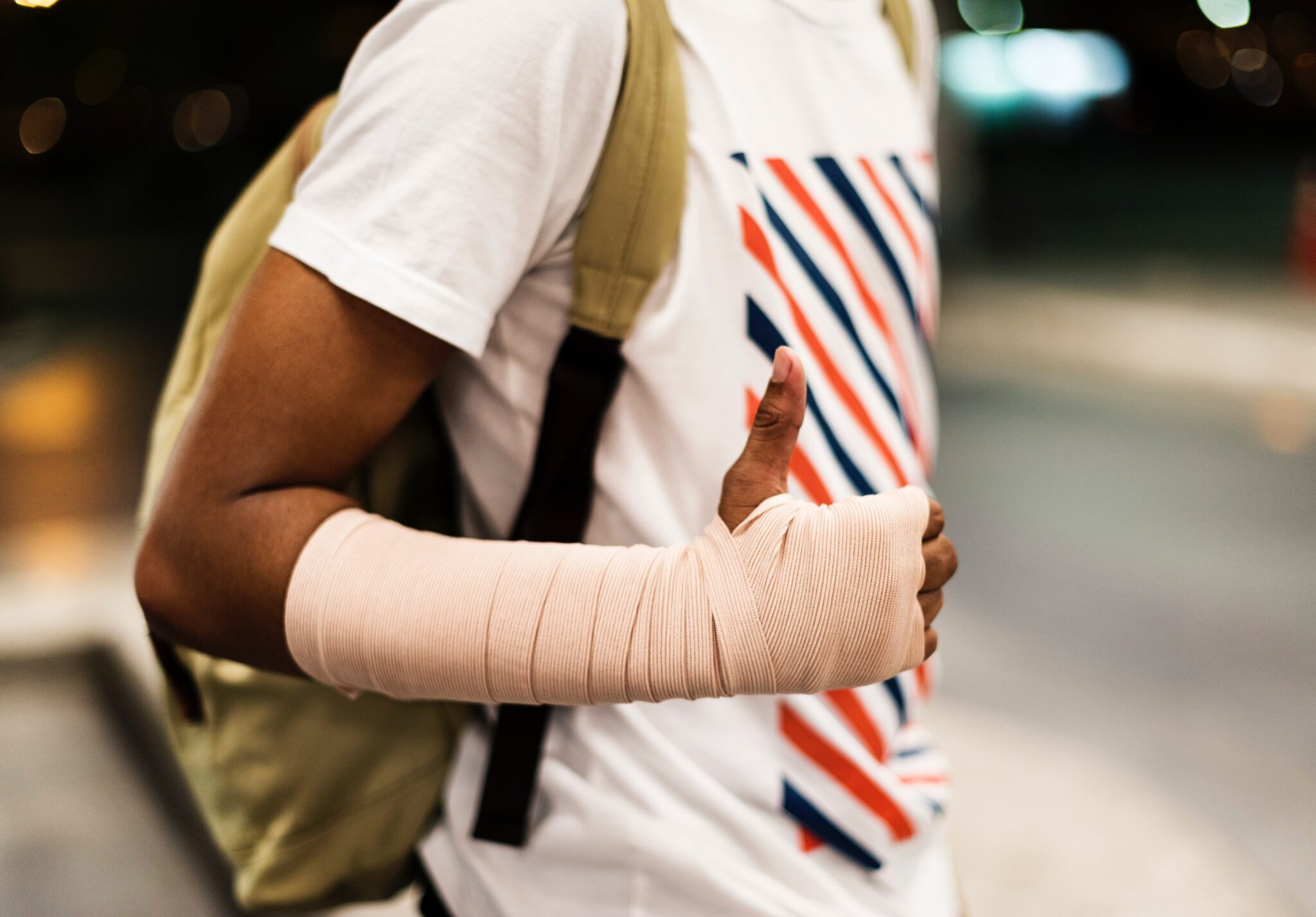 young man with arm bandage giving thumbs up