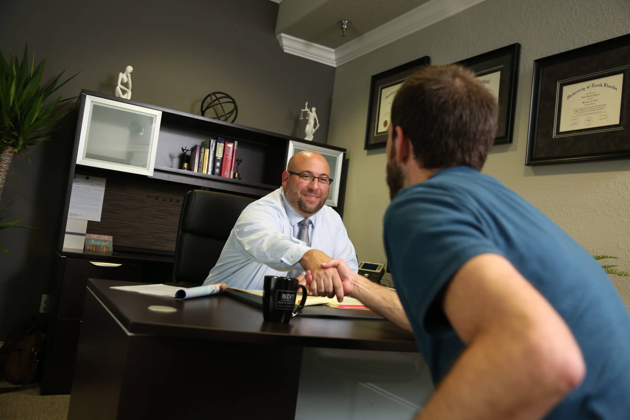 Workers' comp attorney Brian Tadros shaking client's hand
