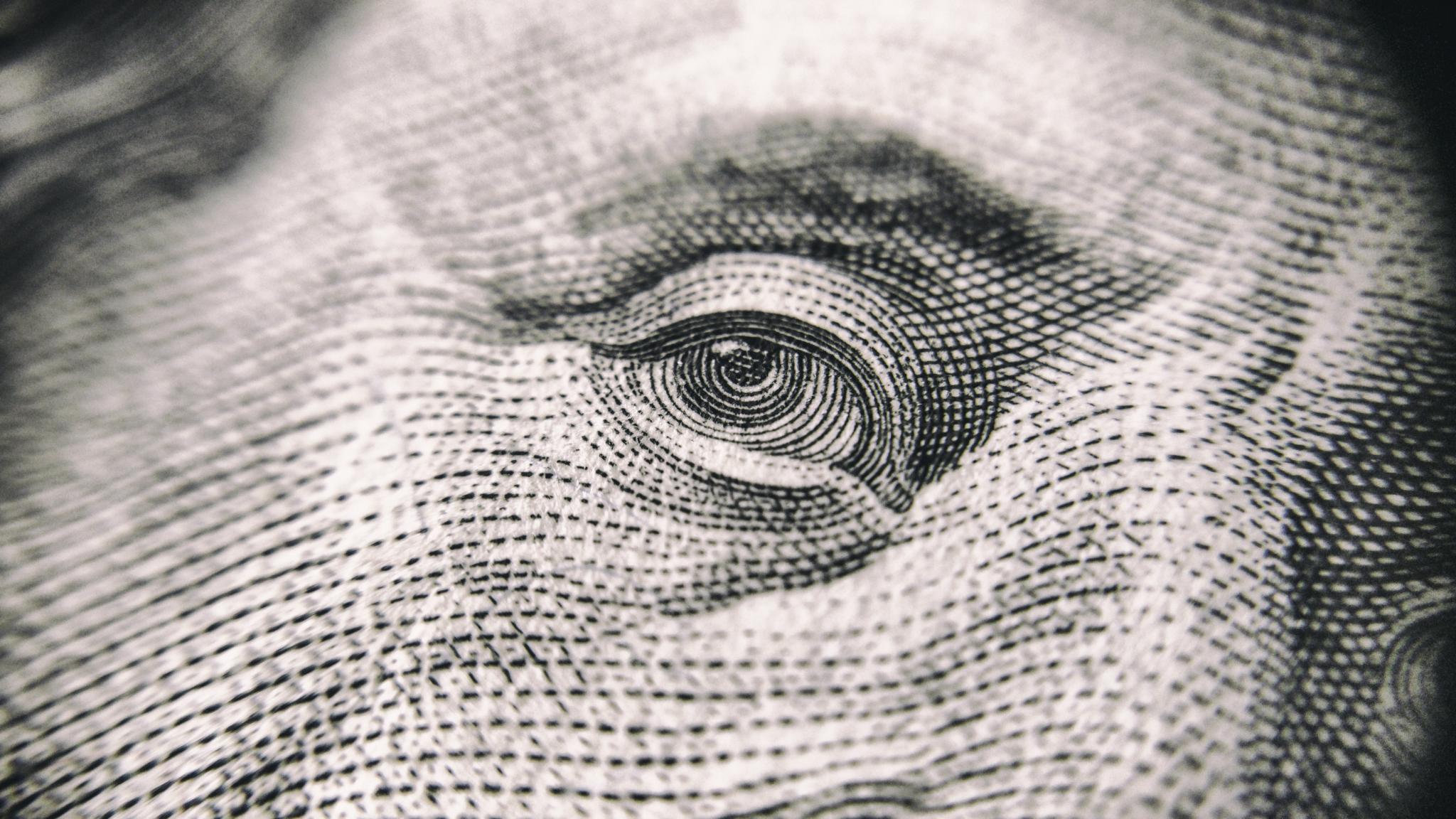 closeup of Benjamin Franklin's eye on 100 dollar bill