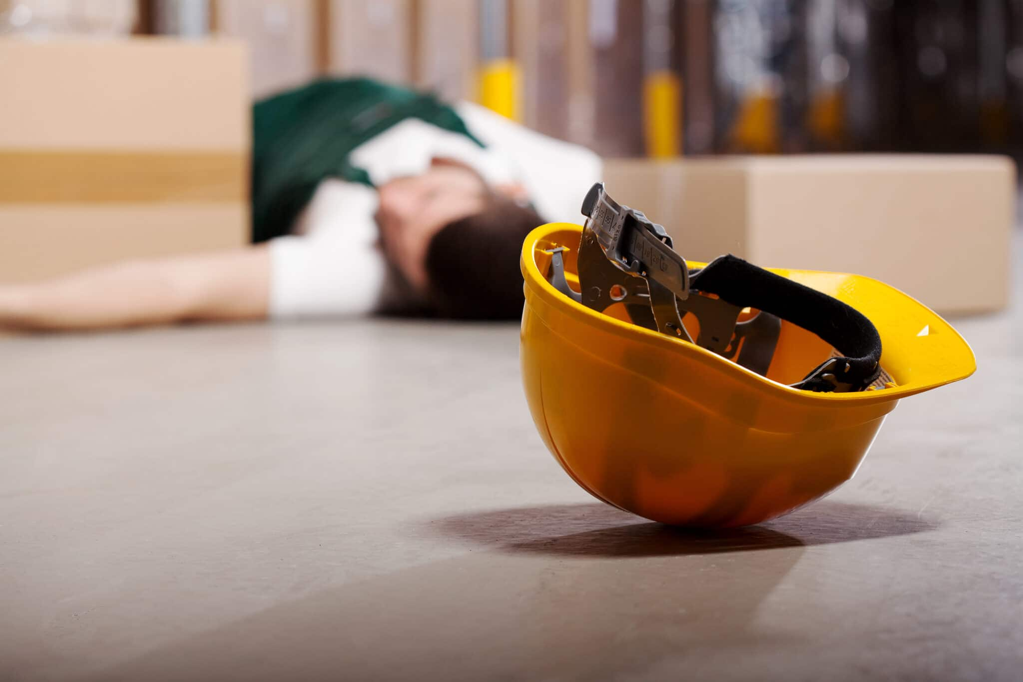 hard hat on ground with blurry injured worker in background