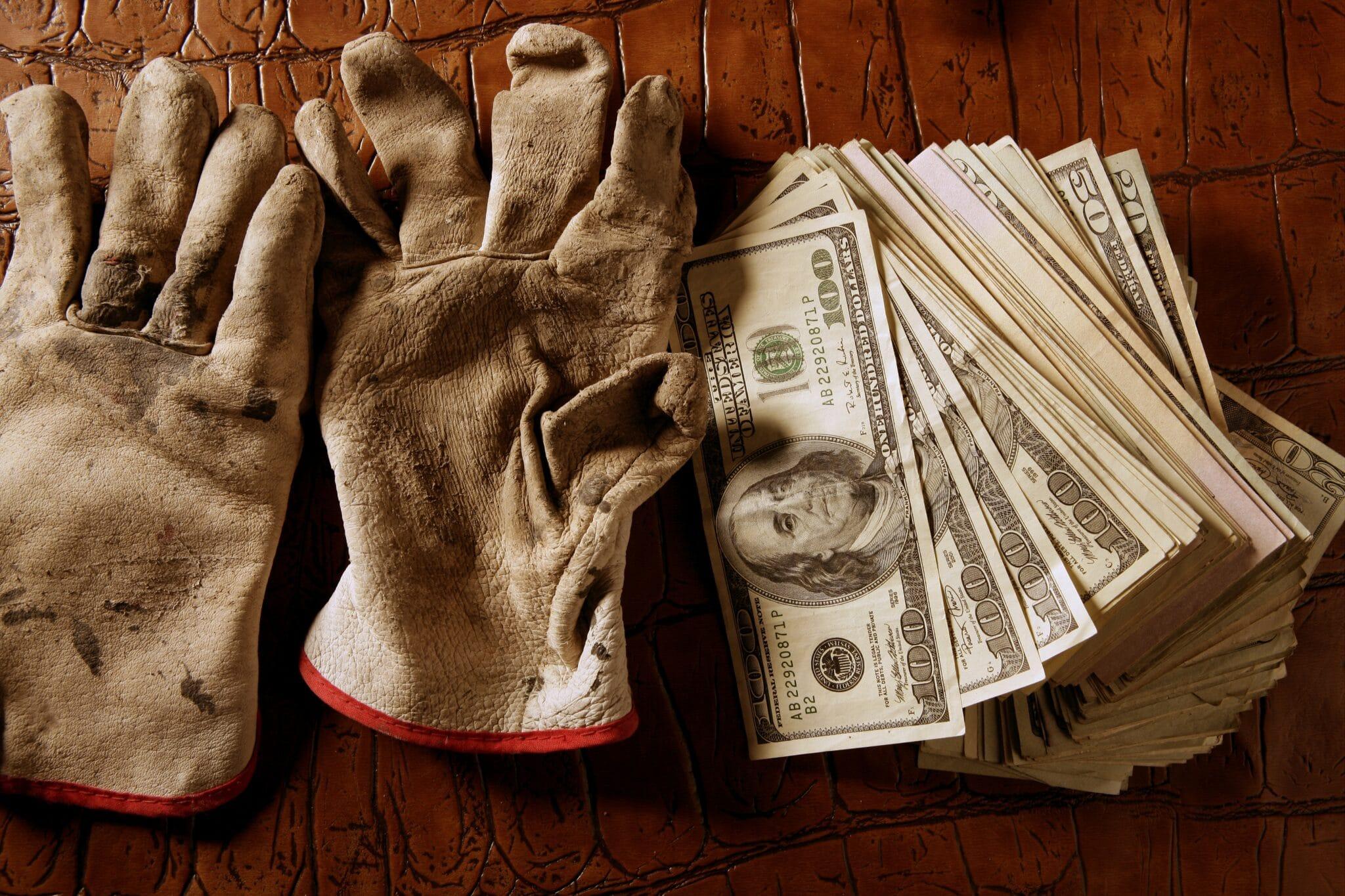 dirty work gloves next to stack of 100 dollar bills