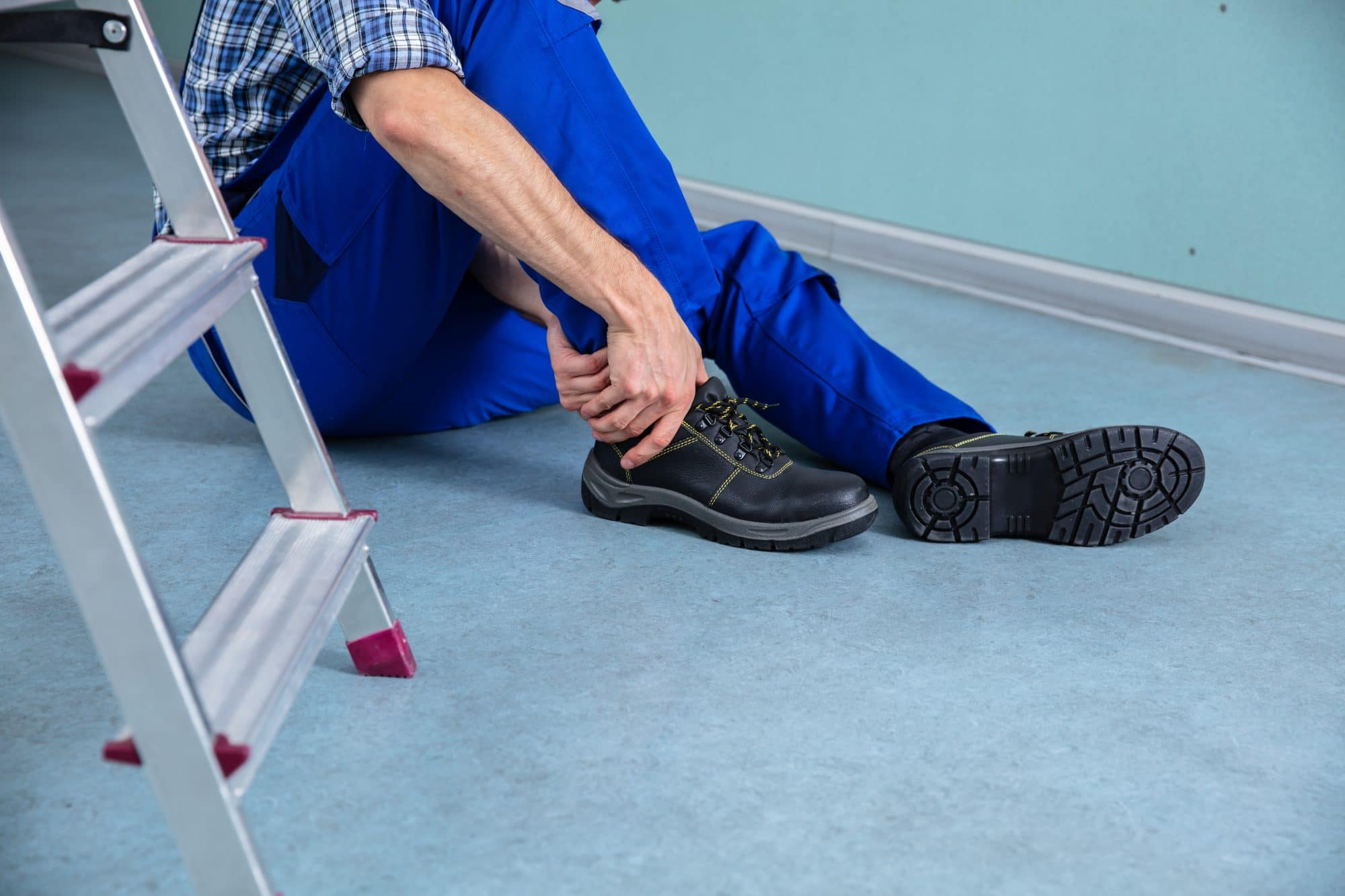man holding ankle next to ladder