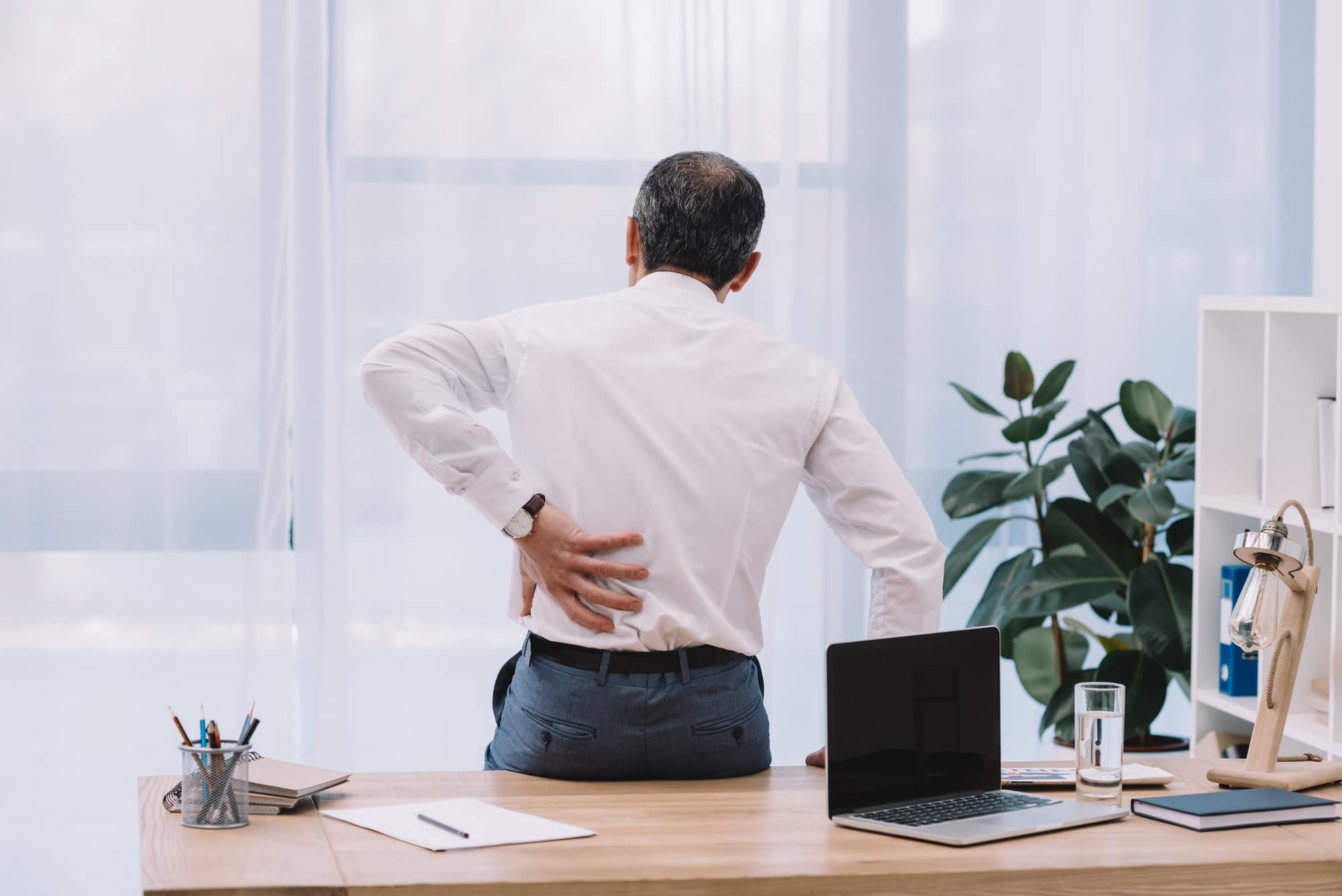 man with back pain sitting on desk