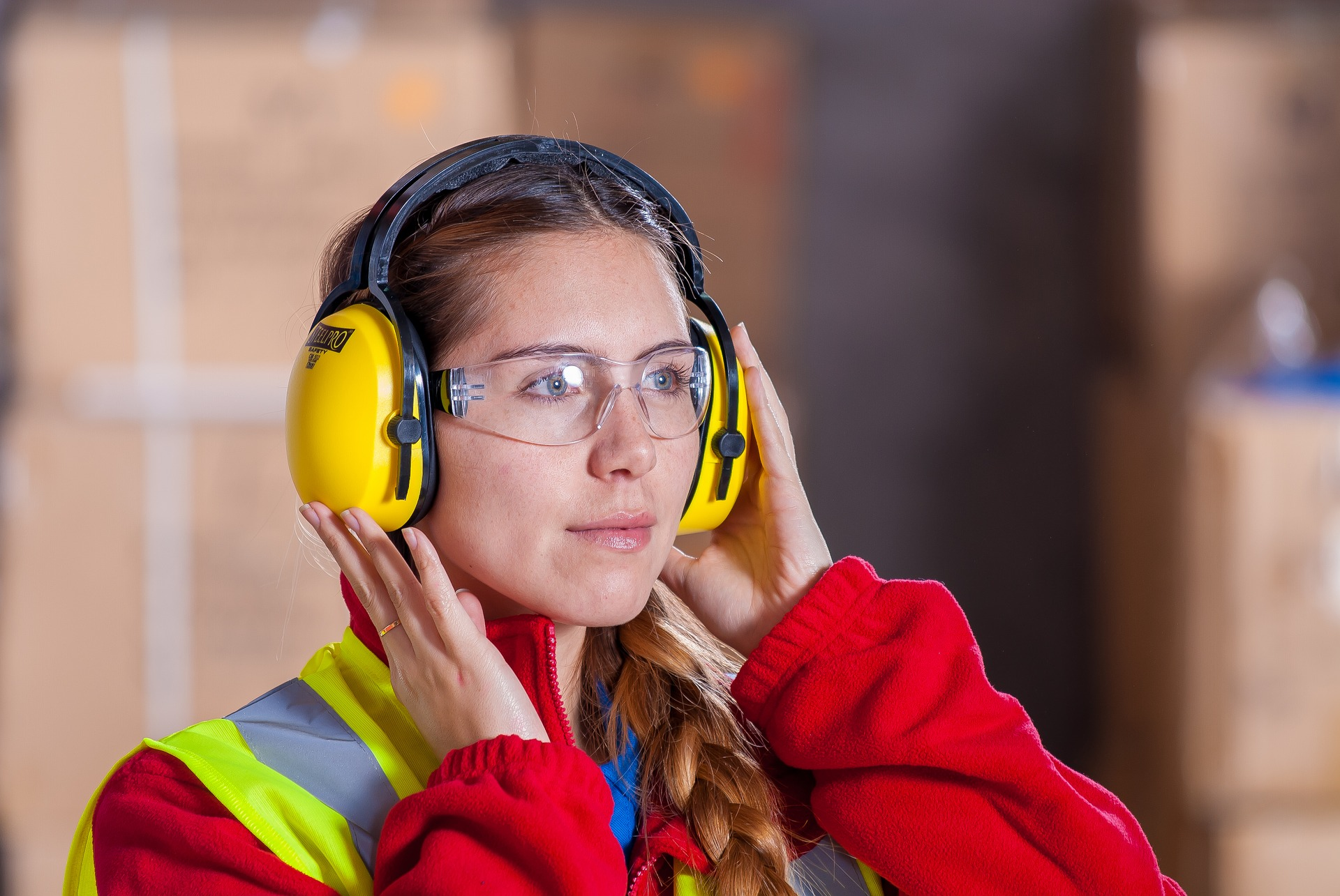 warehouse employee wearing ear protection against loud noise