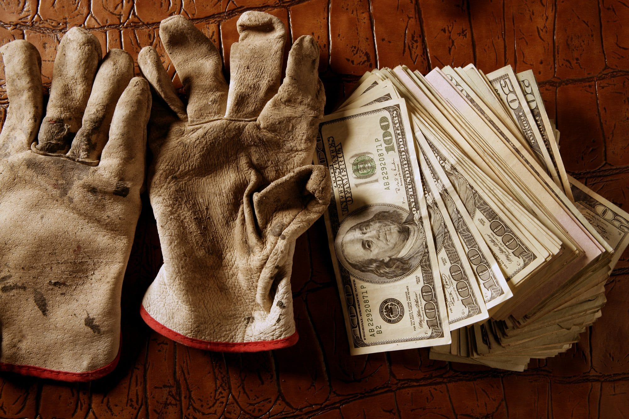 work gloves next to stack of cash