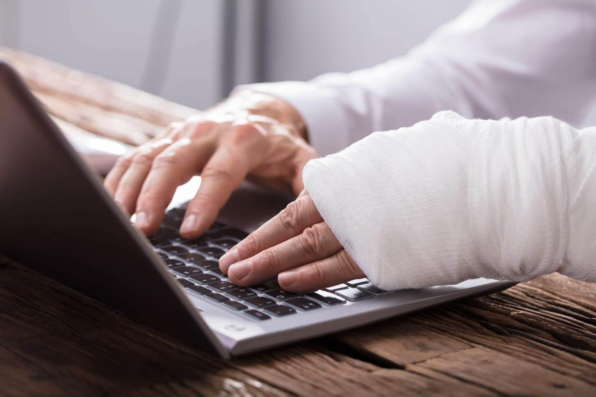 person with bandaged hand working on laptop