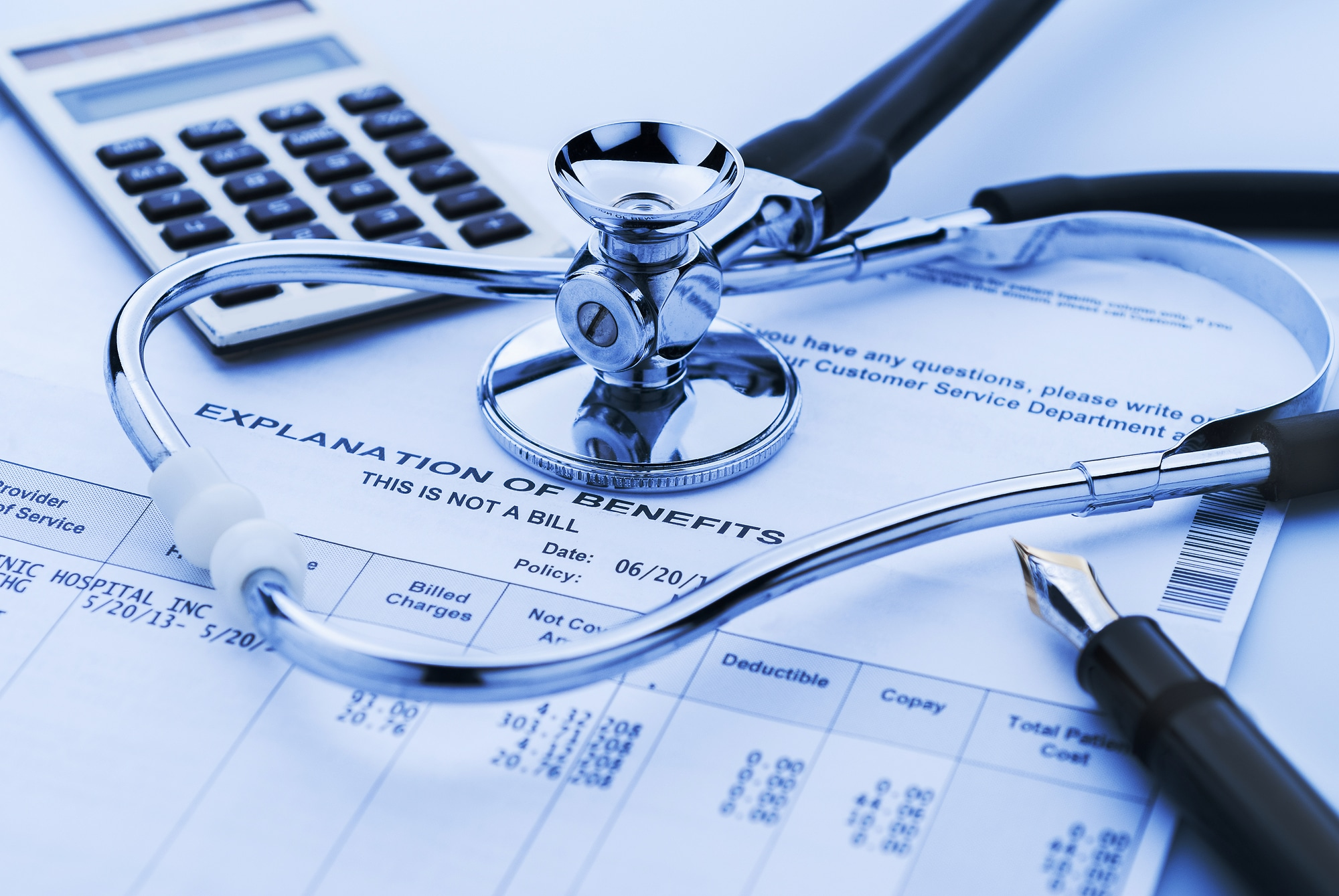 stethoscope and calculator on medical bill