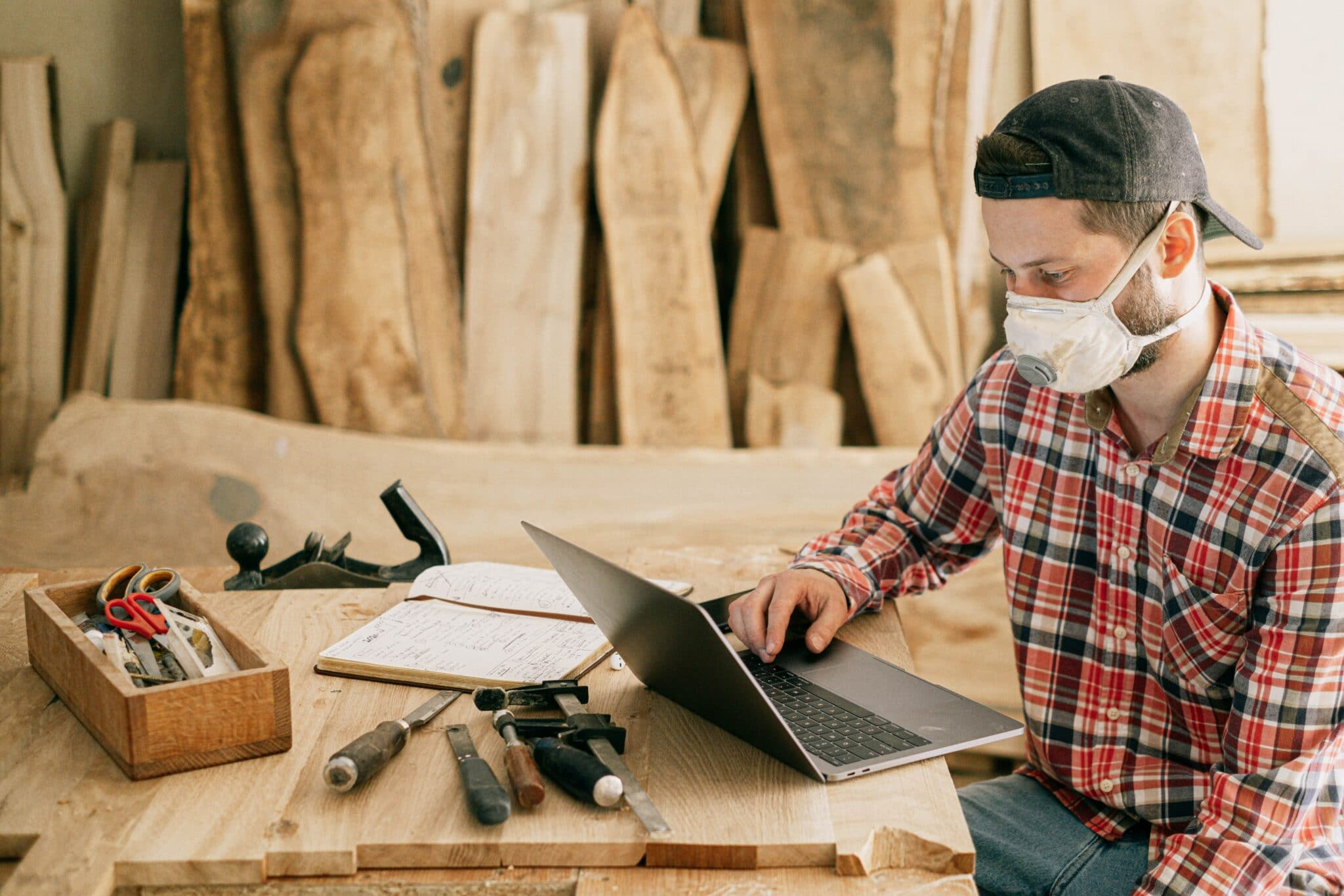 Carpenter with mask on sitting at laptop in workshop