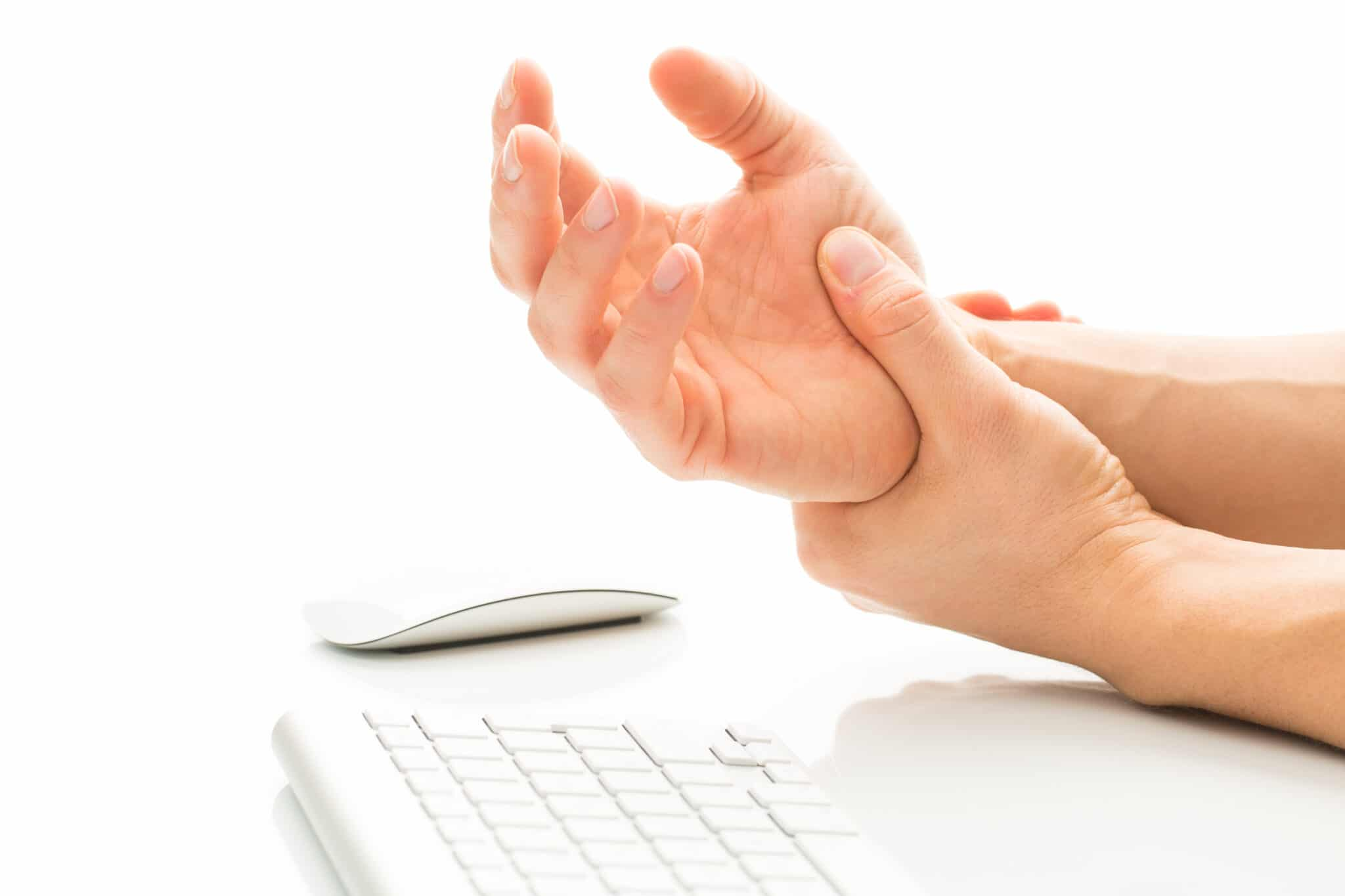 Man holding wrist while at a computer