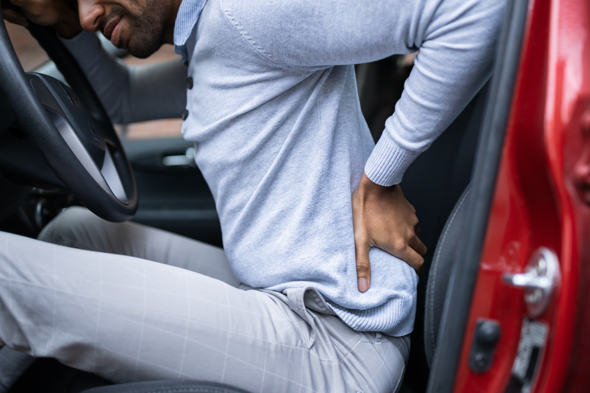 Driver of car holding back in pain
