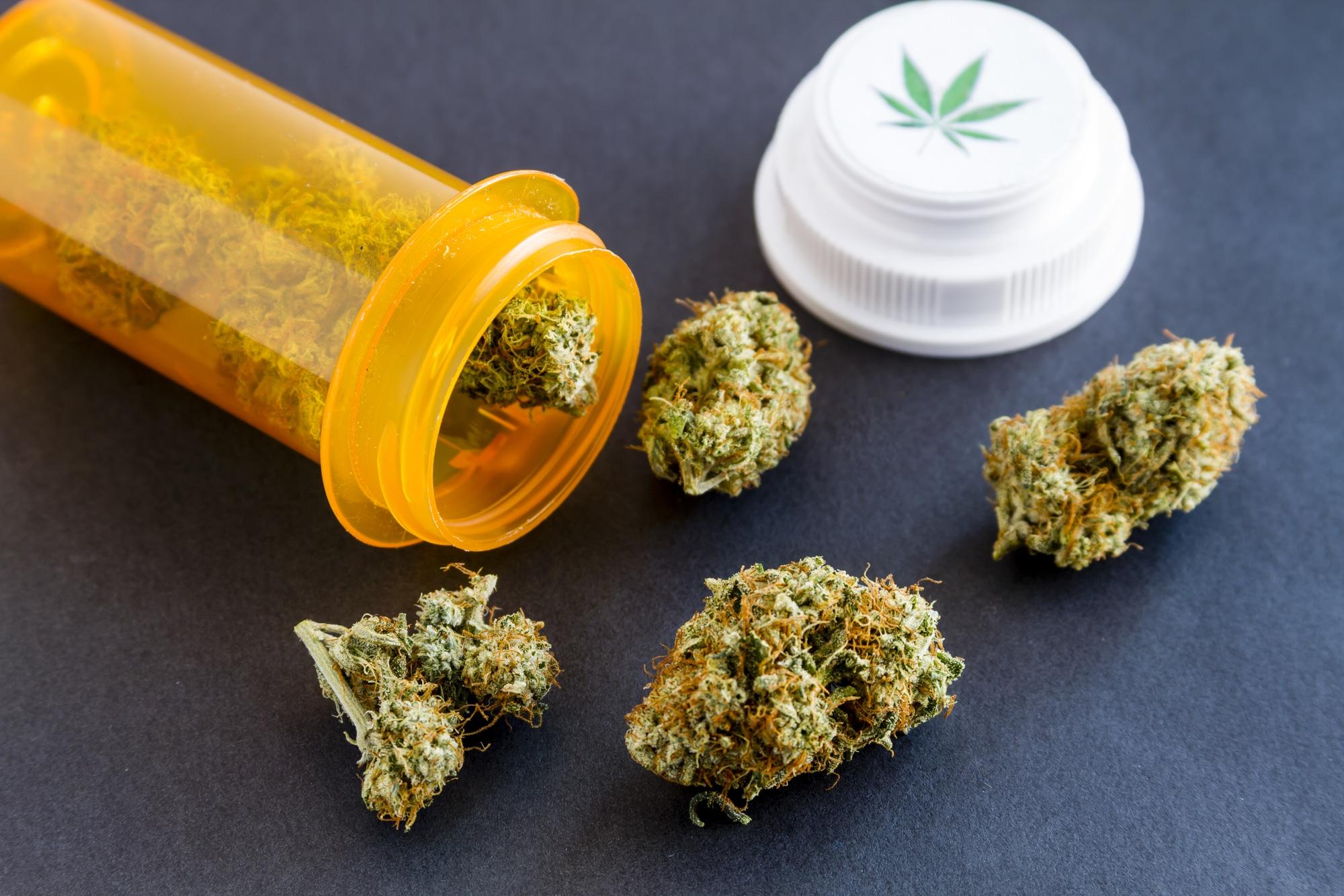 Marijuana buds spilling out of orange prescription bottle